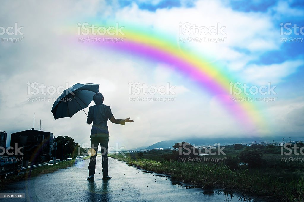 Businessman holding an umbrella, Rainbow and sky after the rain stock photo