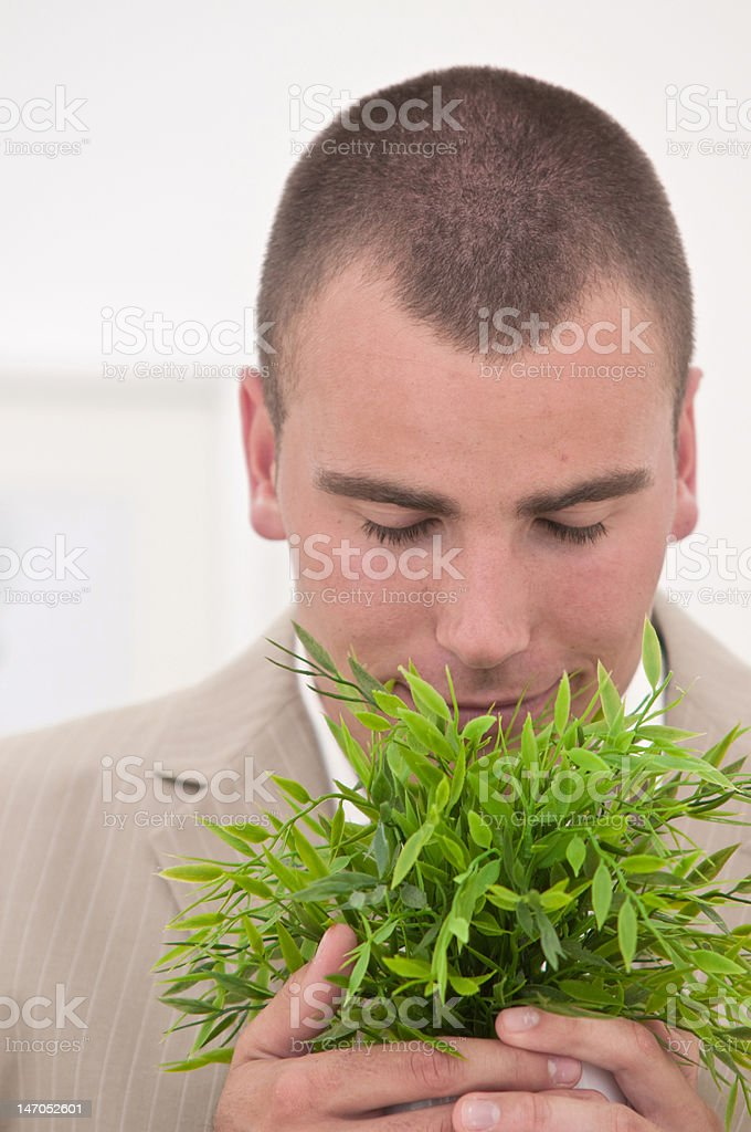 businessman holding and smelling a plant stock photo
