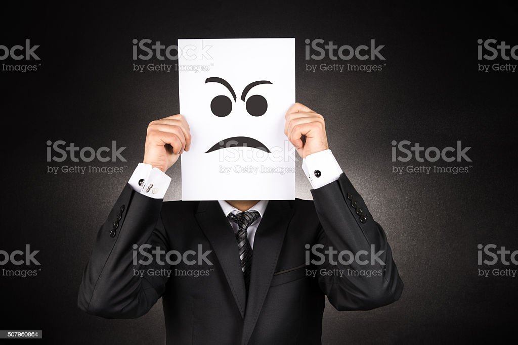 Businessman holding Angry emoji stock photo