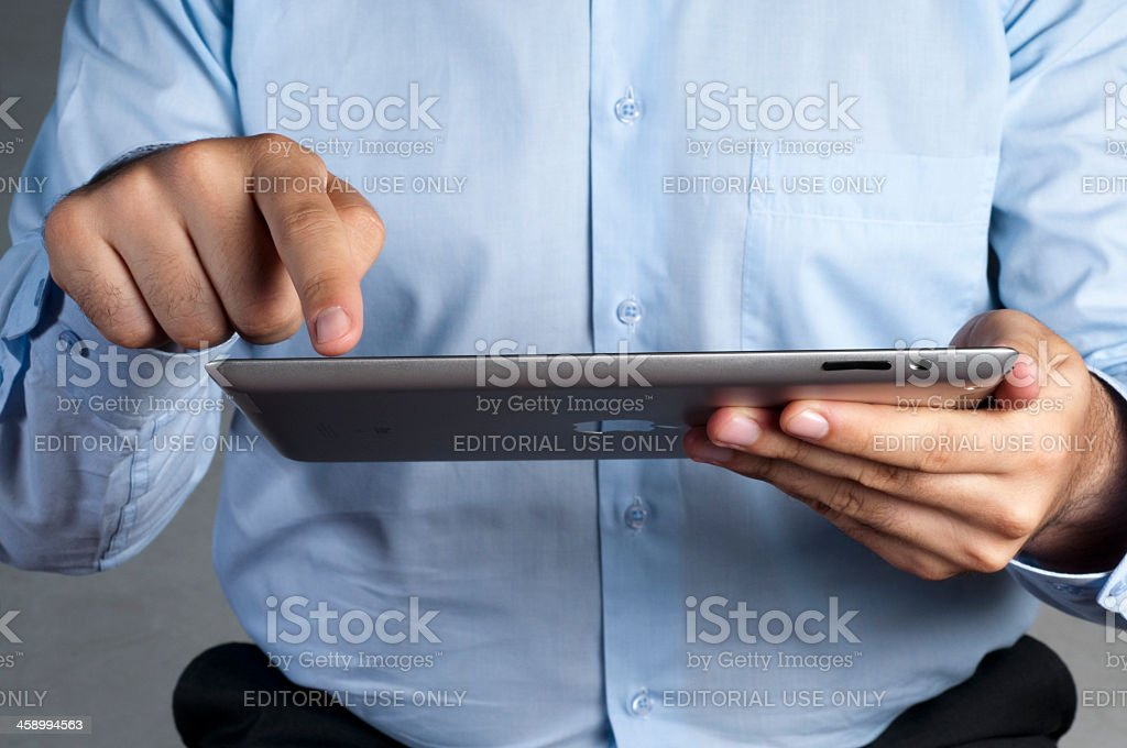 Businessman holding Apple iPad and finger tapping on the screen royalty-free stock photo