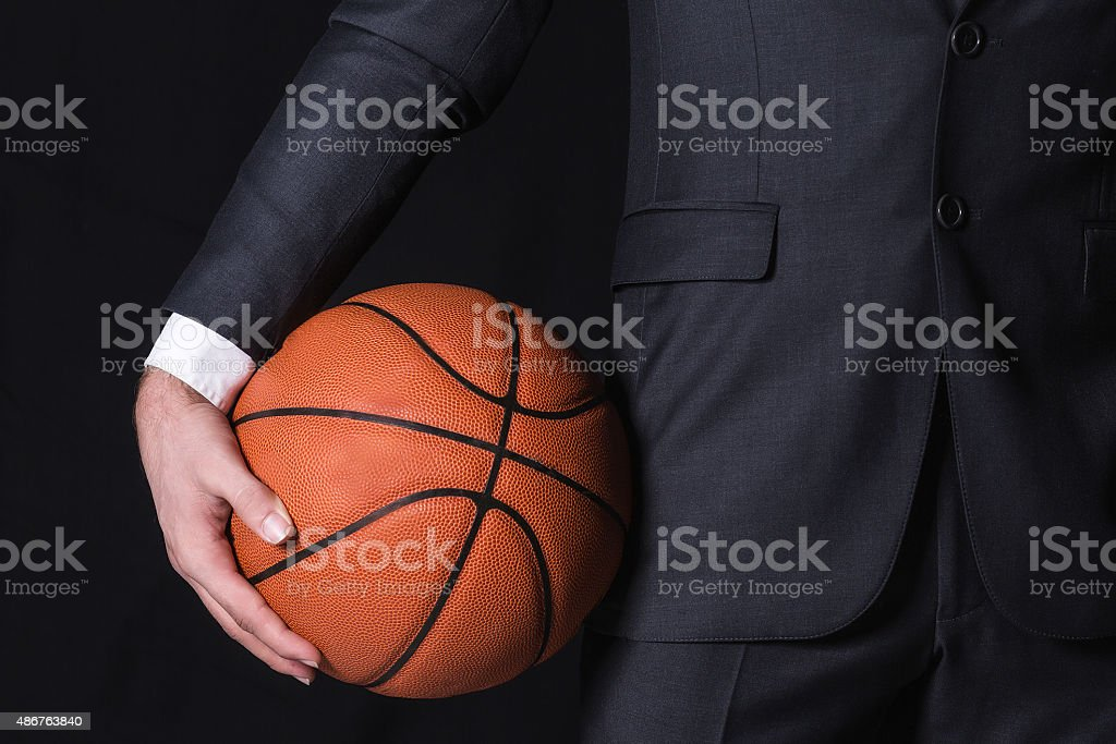 Businessman holding basketball in black background.