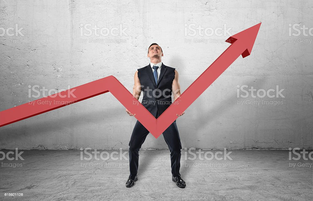 Businessman holding big red line graph with an upturned arrow stock photo