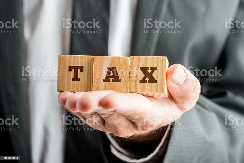 Businessman Holding Blocks with TAX Word stock photo
