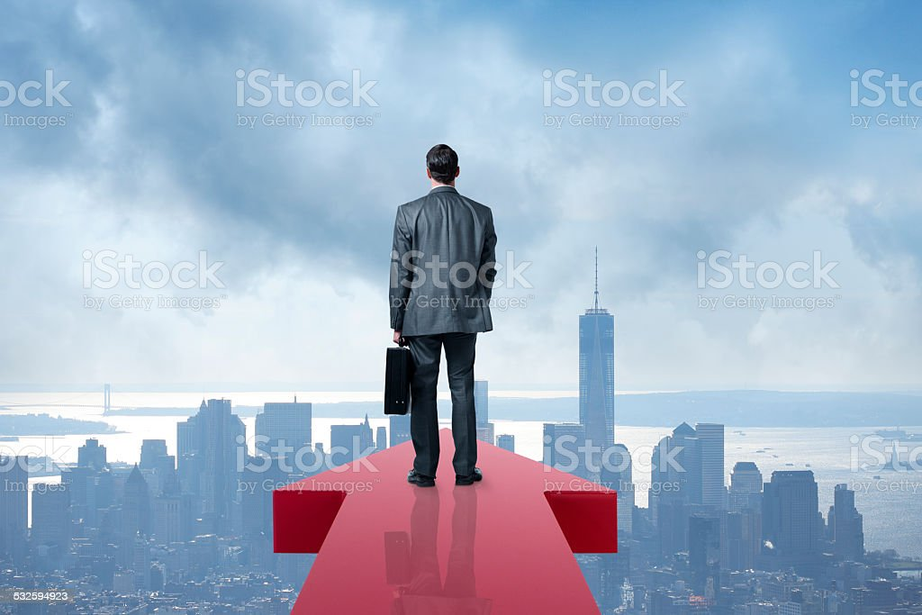 Businessman Holding Briefcase At The End Of An Arrow stock photo