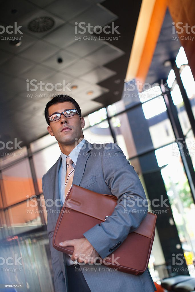 Businessman holding briefcase in office royalty-free stock photo
