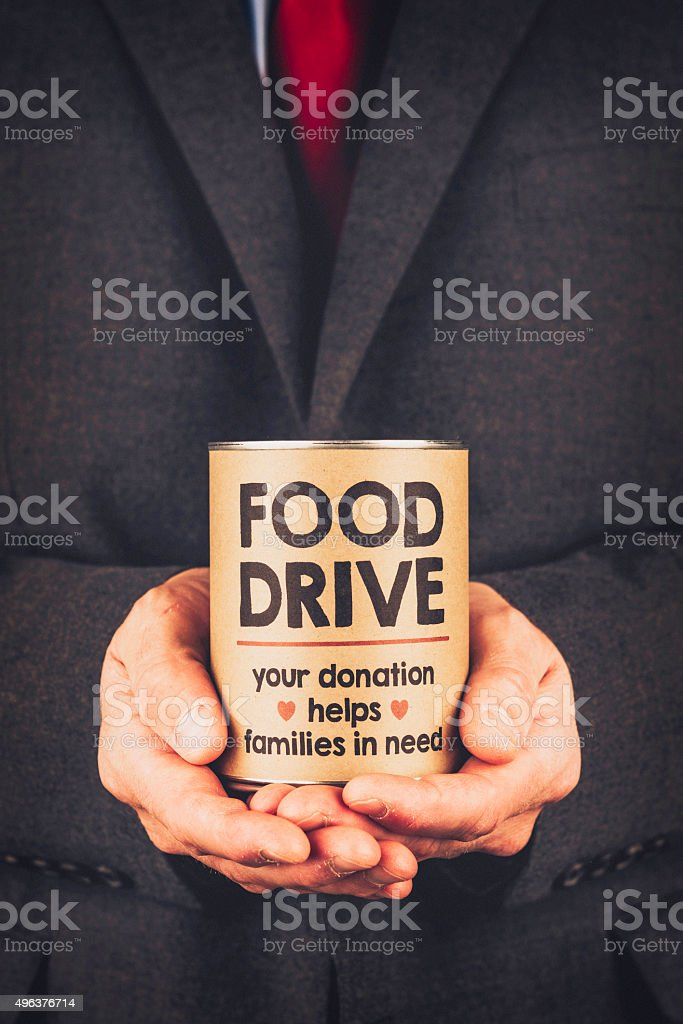 Businessman holding canned food for food drive stock photo