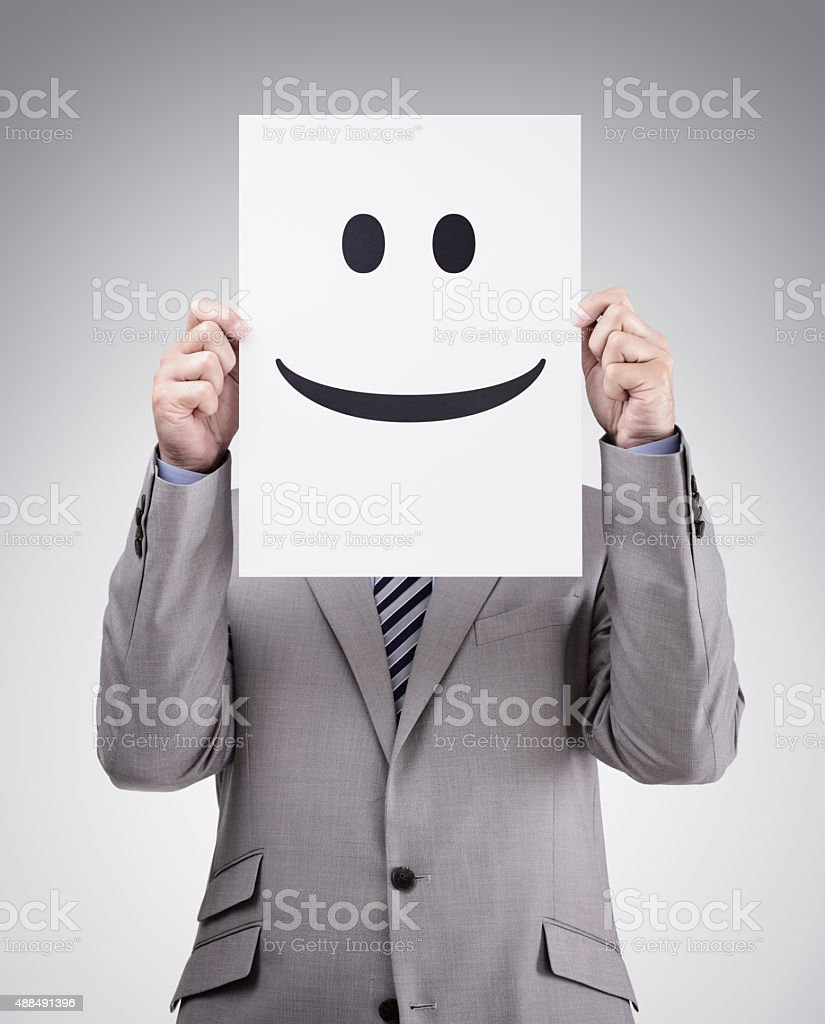 Businessman holding card with smiley face stock photo