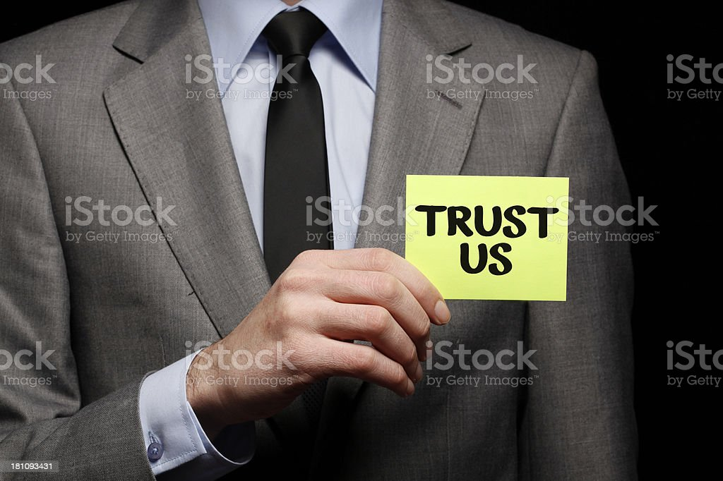 Businessman Holding Card with text TRUST US royalty-free stock photo