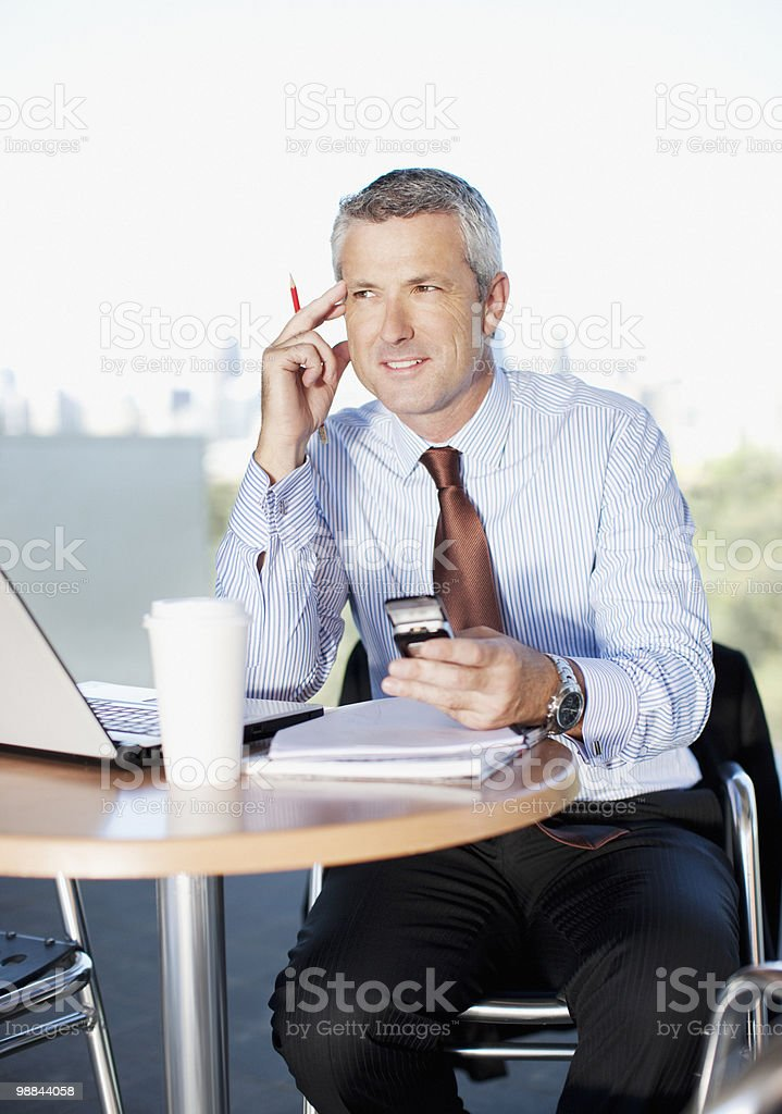 Businessman holding cell phone in cafe royalty-free stock photo