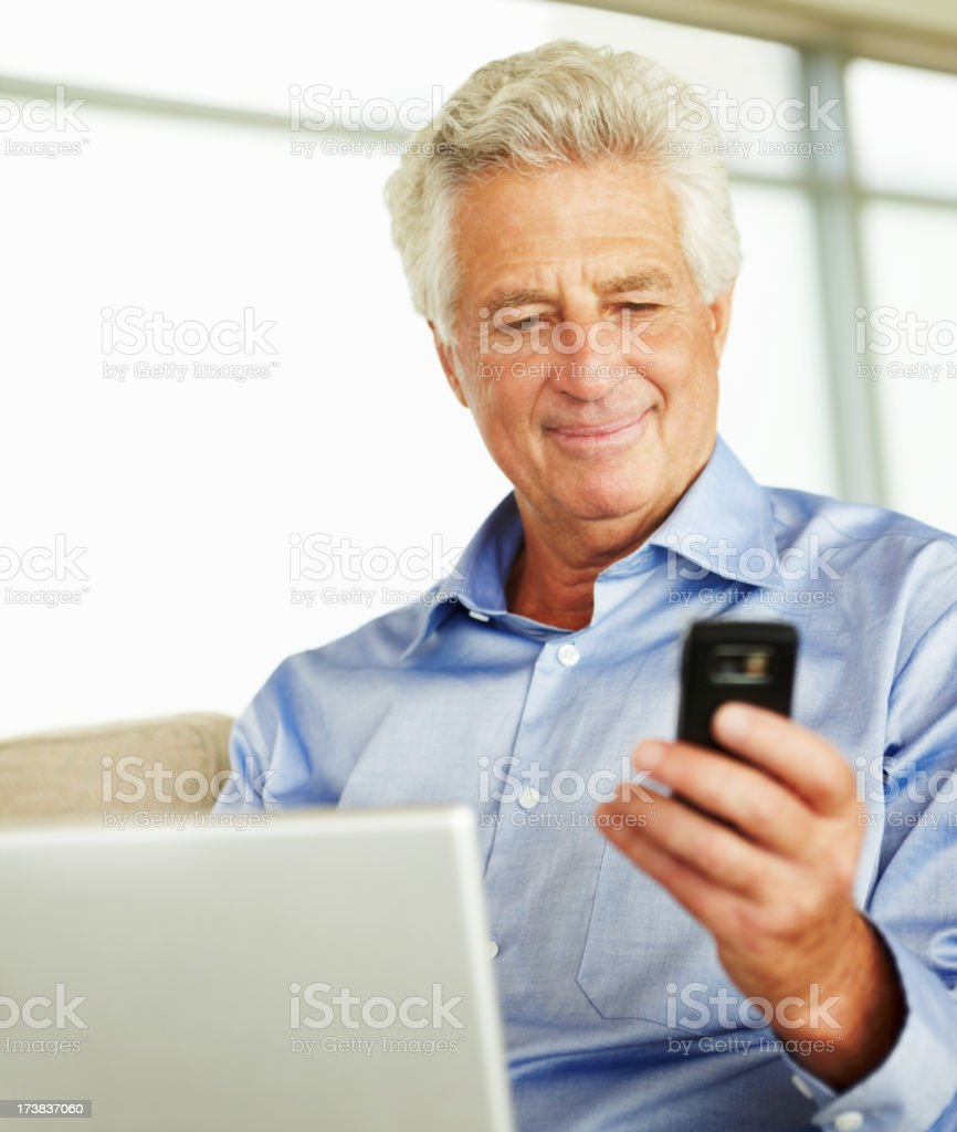 Businessman holding cellphone with laptop royalty-free stock photo