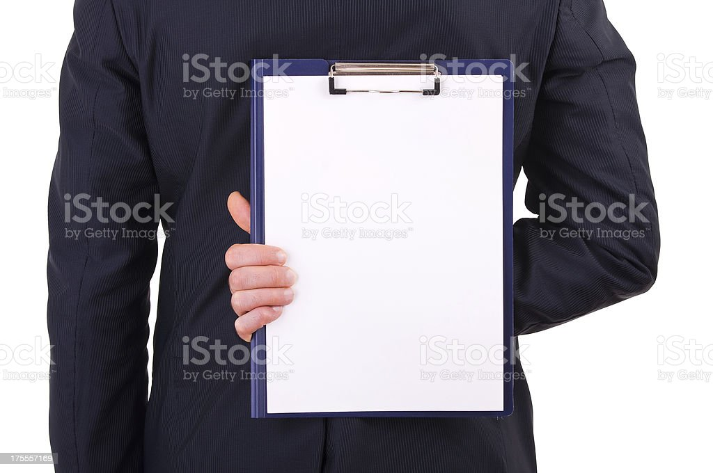 Businessman holding clipboard behind back stock photo