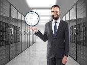 Businessman holding clock icon on virtual screen