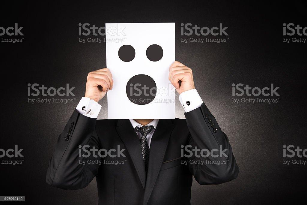 Businessman holding confused emoji stock photo
