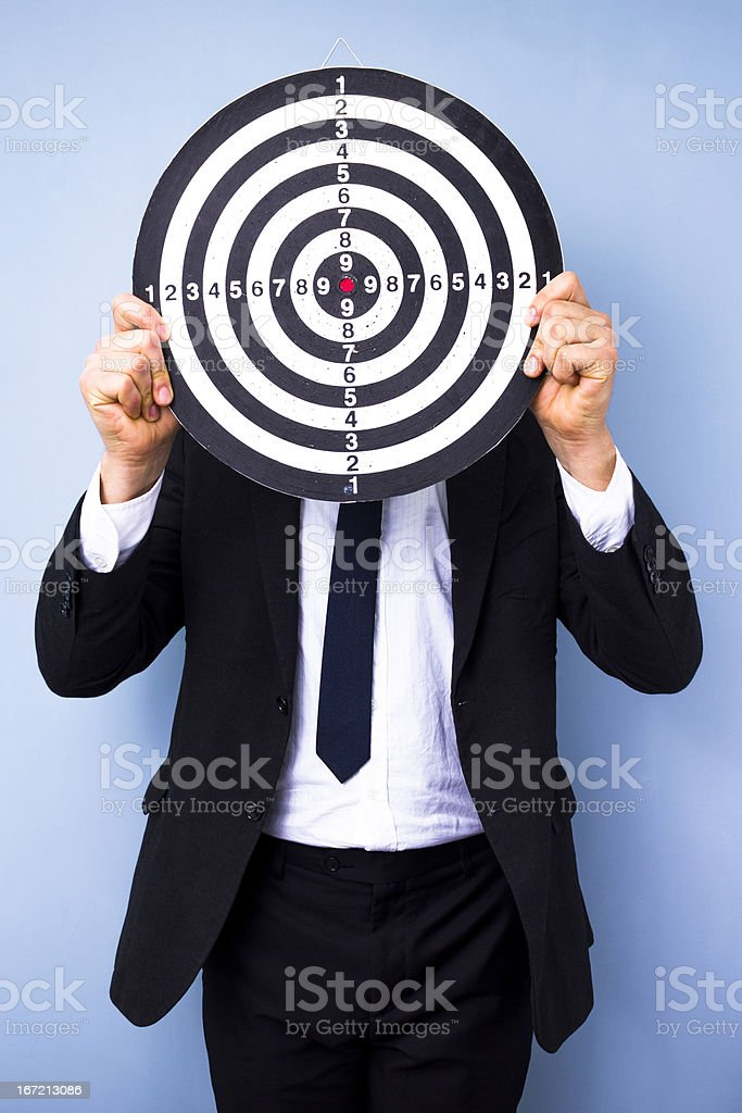 Businessman holding dartboard stock photo