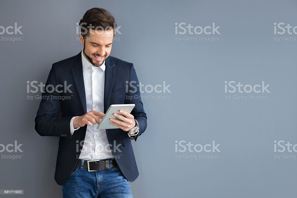 Businessman holding digital tablet in an office building hallway. stock photo