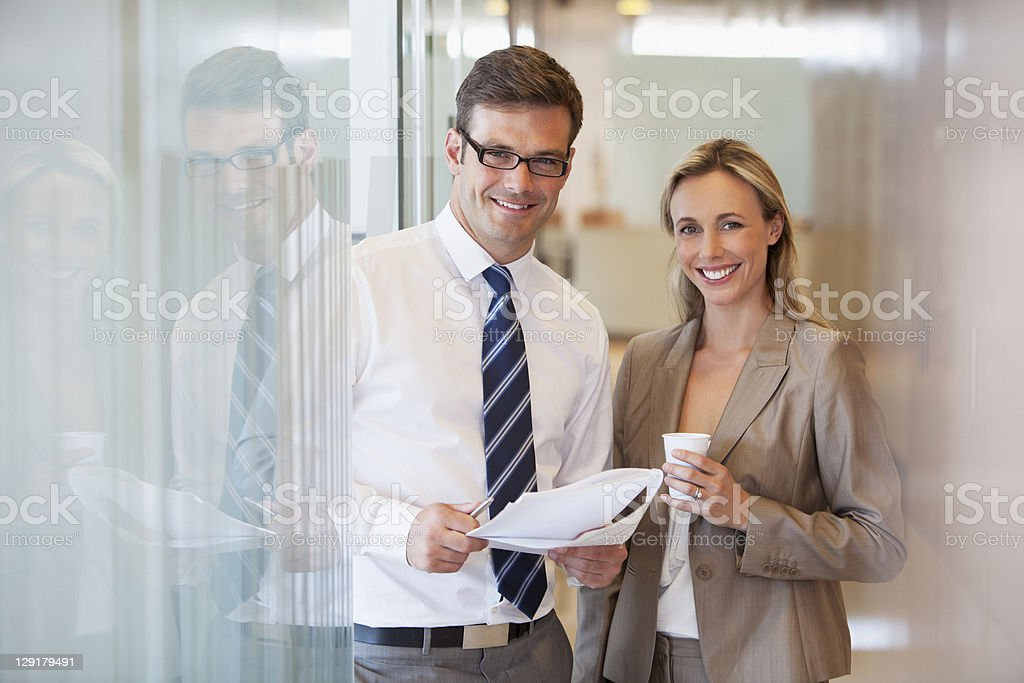 Businessman holding document while standing with female coworker royalty-free stock photo