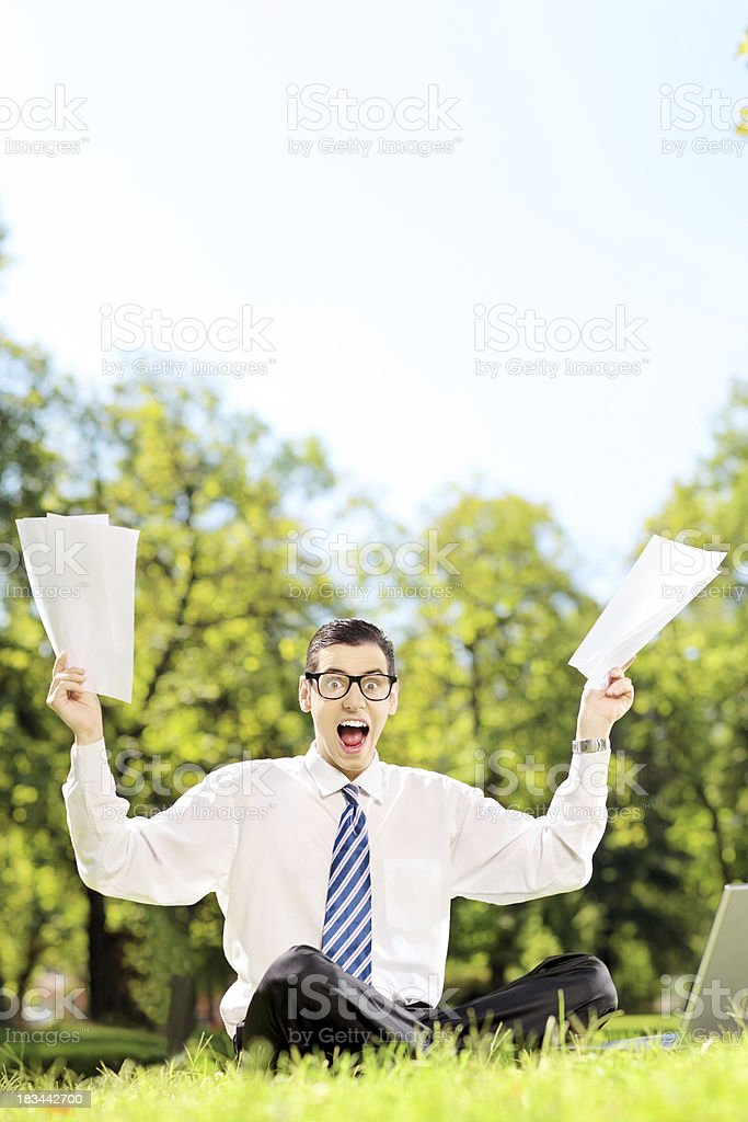 Businessman holding documents and screaming in a park royalty-free stock photo