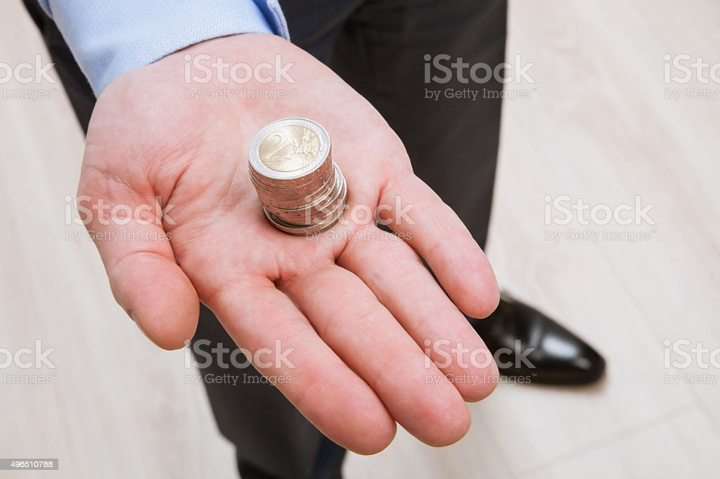 Businessman holding euro coins stock photo