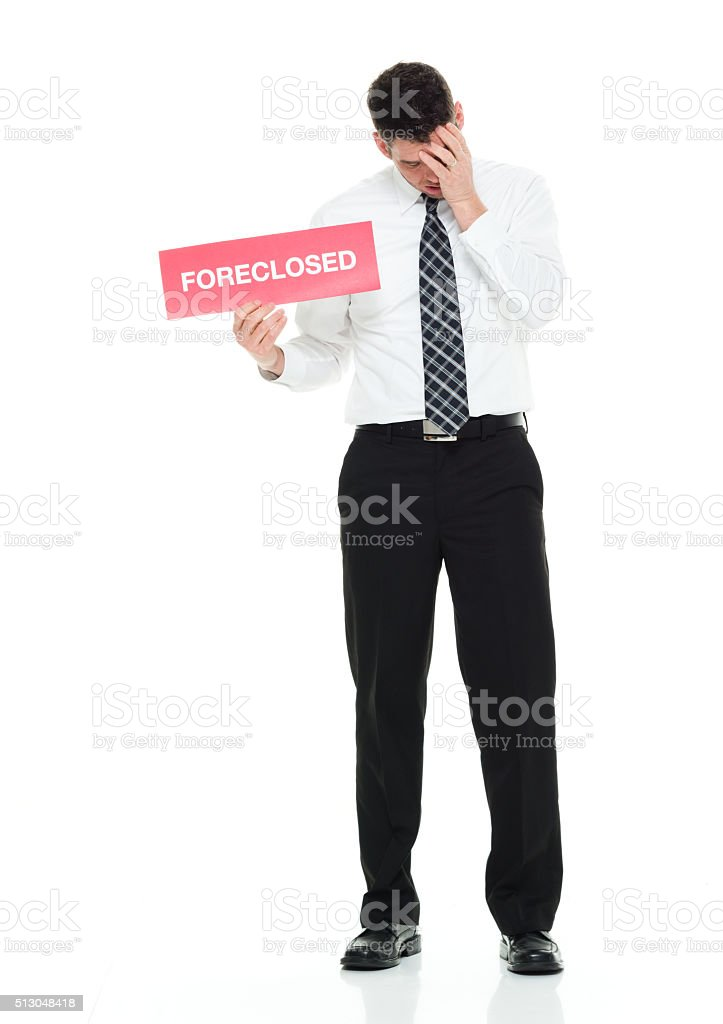 Businessman holding foreclosed sign stock photo