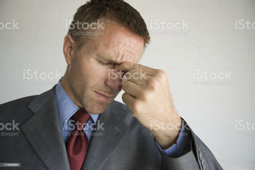 Businessman Holding Forehead to Relieve Headache stock photo
