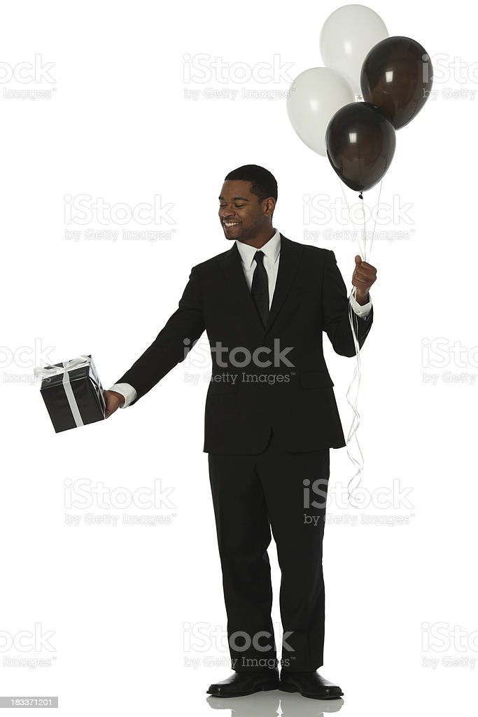 Businessman holding gift and balloons royalty-free stock photo