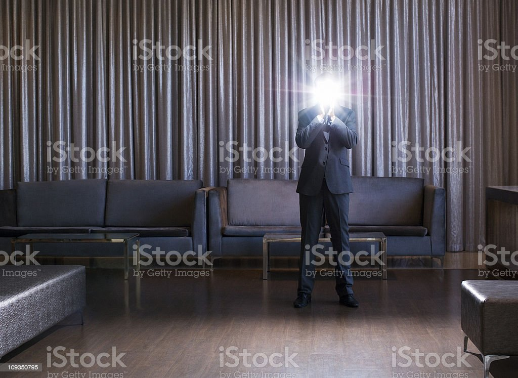 Businessman holding glowing light in hotel lobby royalty-free stock photo