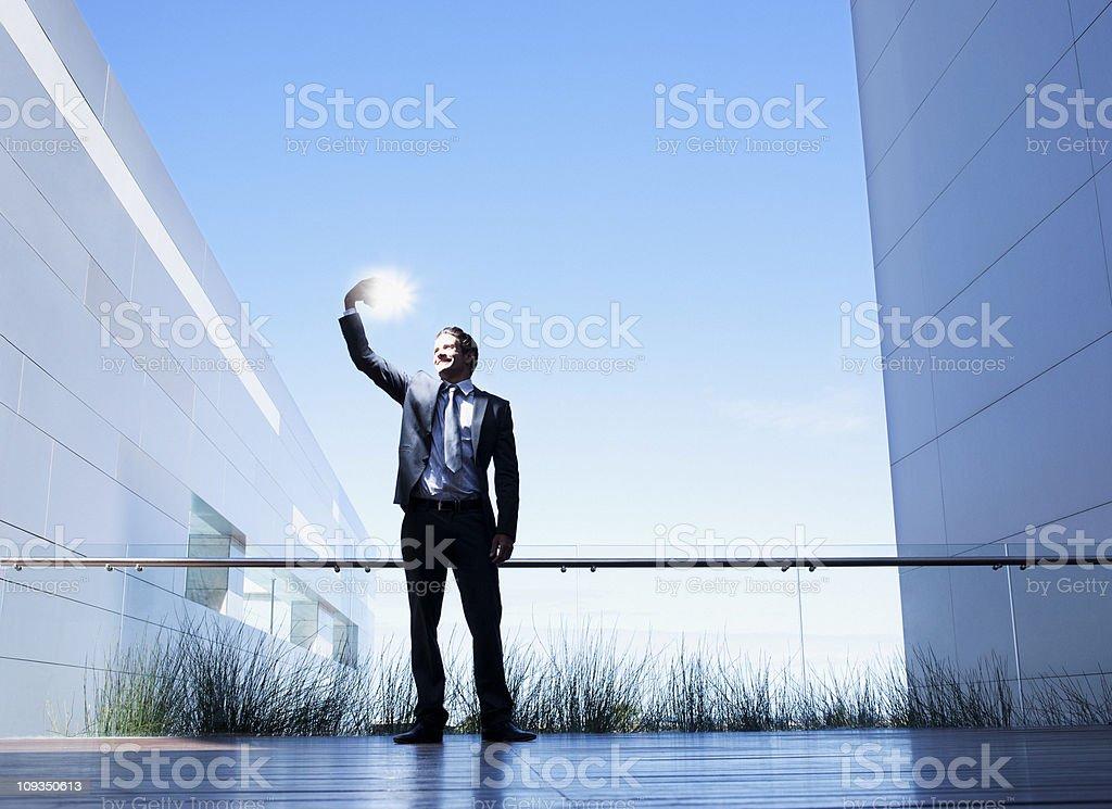 Businessman holding glowing light on balcony royalty-free stock photo