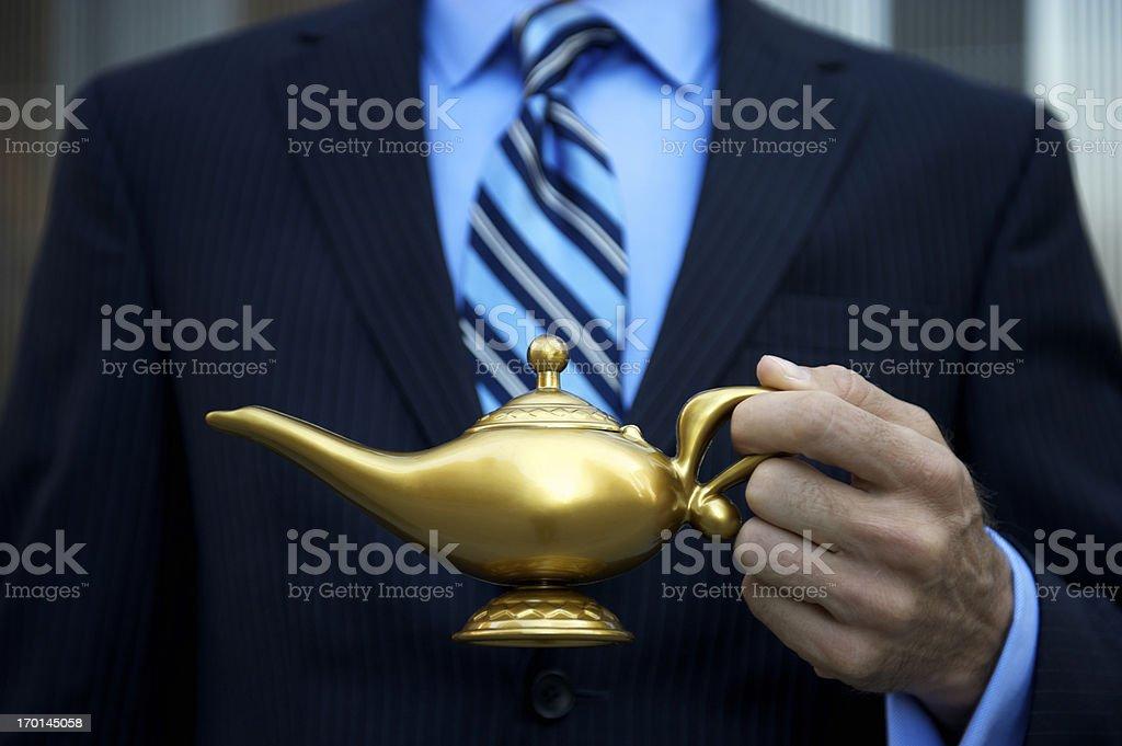 Businessman Holding Golden Magic Lamp stock photo