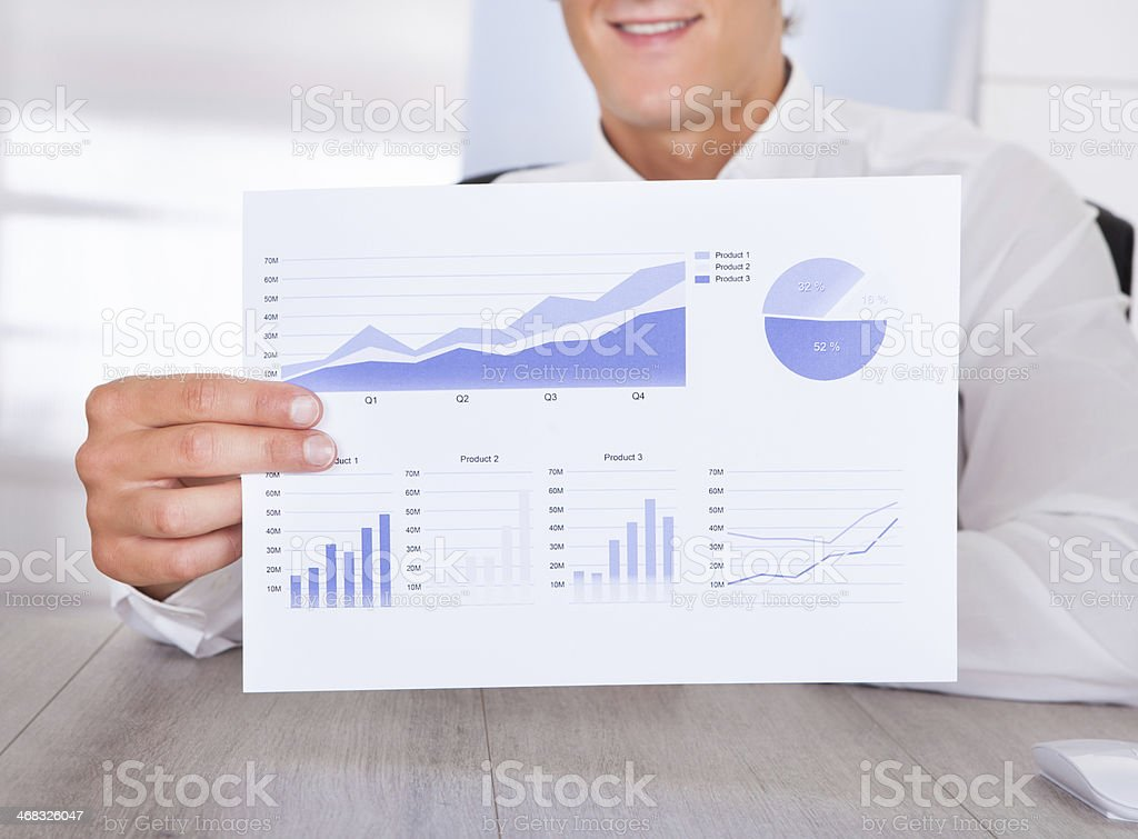 Businessman Holding Graph Printed On Paper stock photo