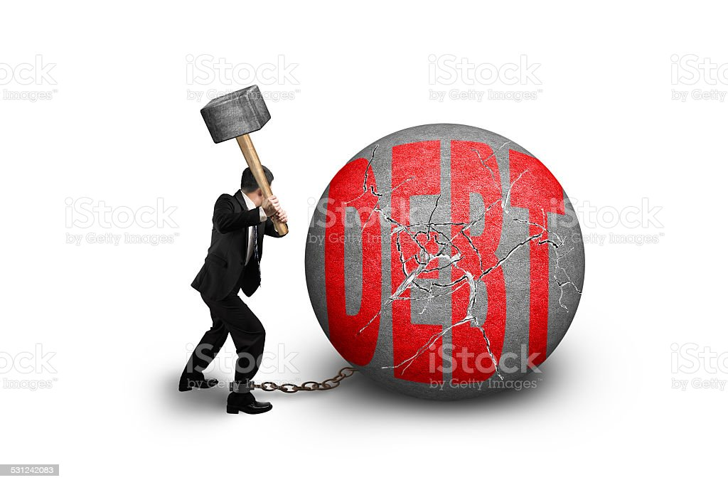 Businessman holding hammer hitting cracked DEBT ball isolated on stock photo