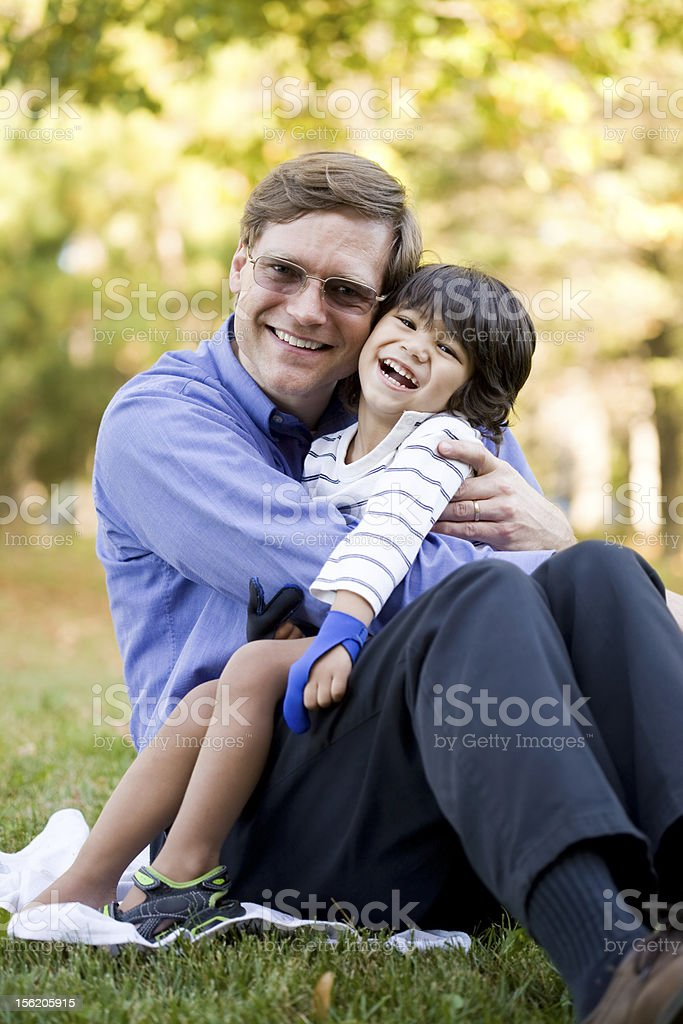 Businessman holding his disabled son on grass royalty-free stock photo