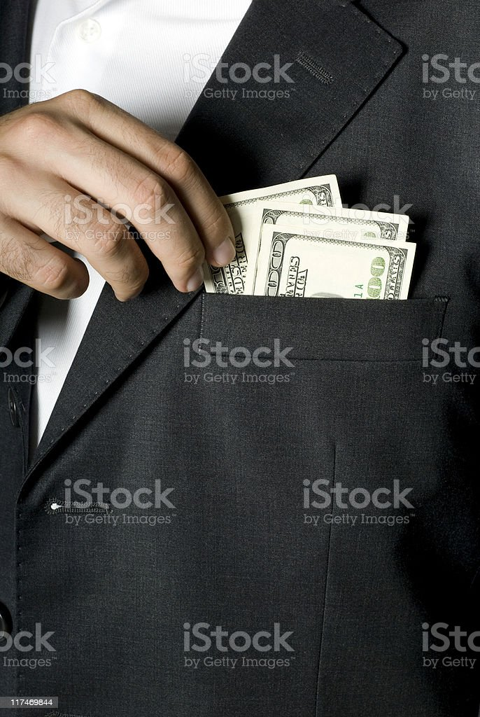 Businessman holding hundred dollar notes in jacket pocket, close-up royalty-free stock photo
