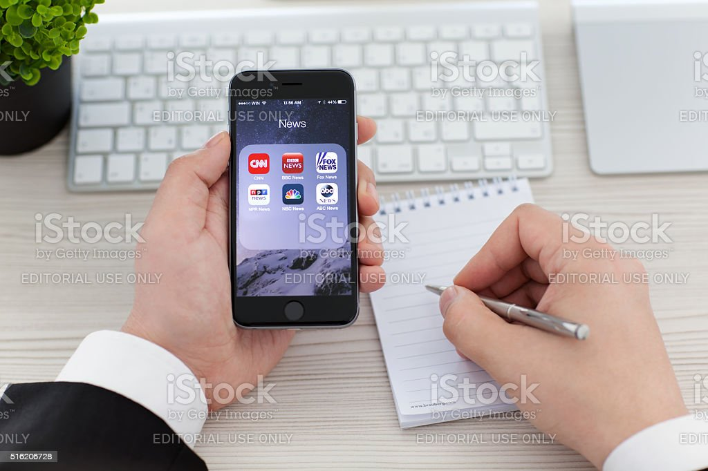 Businessman holding iPhone 6 Space Gray with News applications stock photo