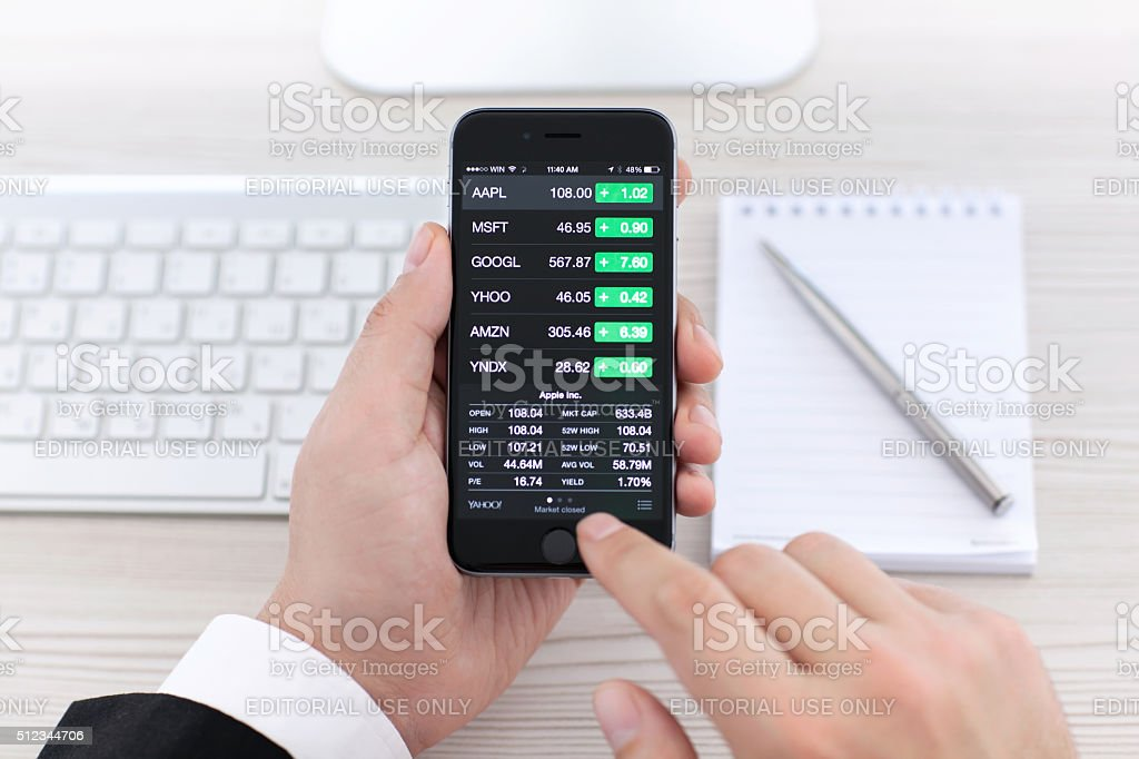 Businessman holding iPhone 6 with application Stocks of Apple stock photo