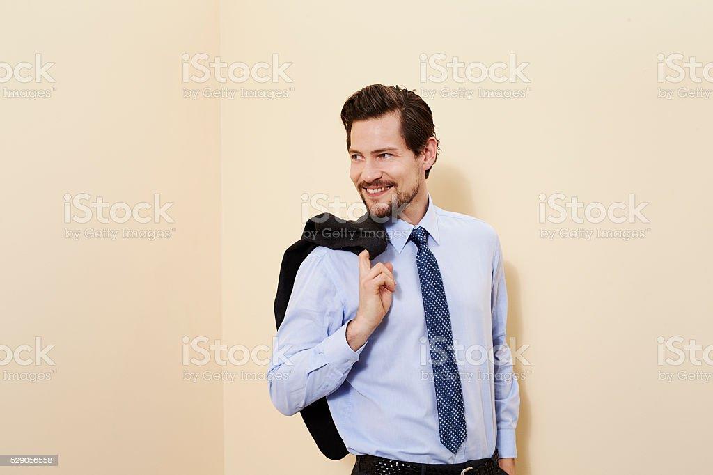 Businessman holding jacket, smiling stock photo