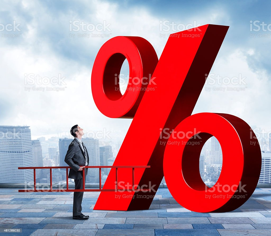 Businessman Holding Ladder Looking Up At Percentage Sign stock photo