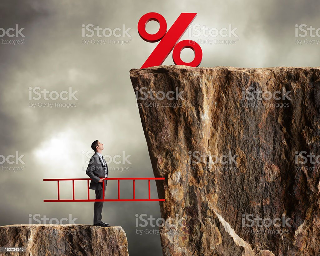 Businessman holding ladder staring up at higher interest rates stock photo