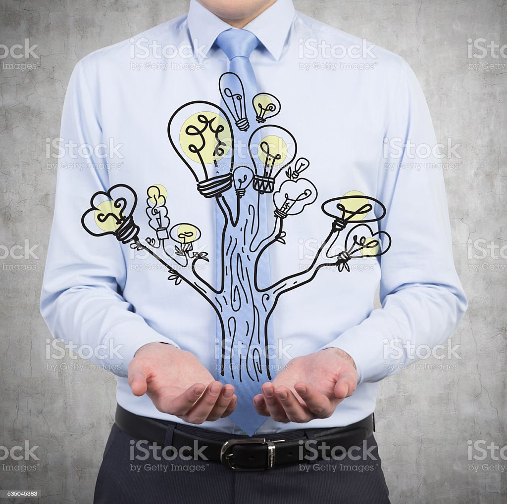 businessman holding lamp tree stock photo