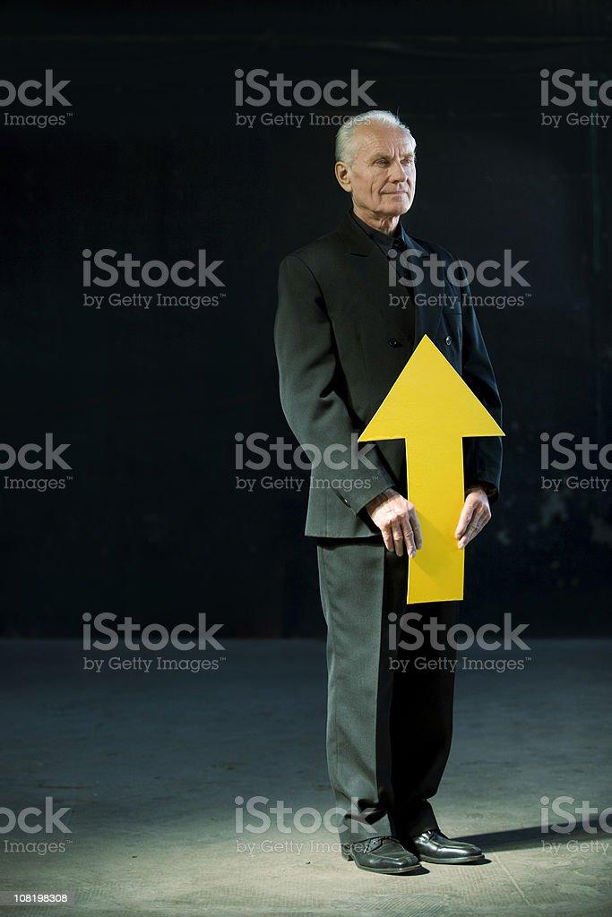 Businessman Holding Large Arrow Pointing Upwards royalty-free stock photo