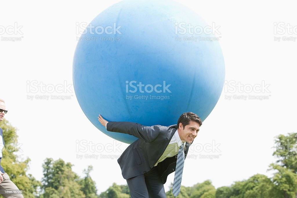Businessman holding large ball on back stock photo