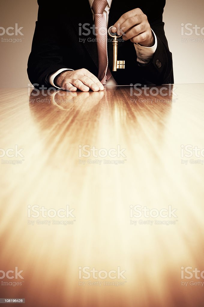Businessman Holding Large Key stock photo
