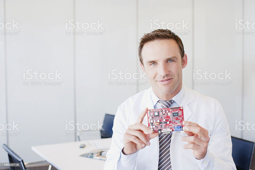 Businessman holding microchip in office royalty-free stock photo