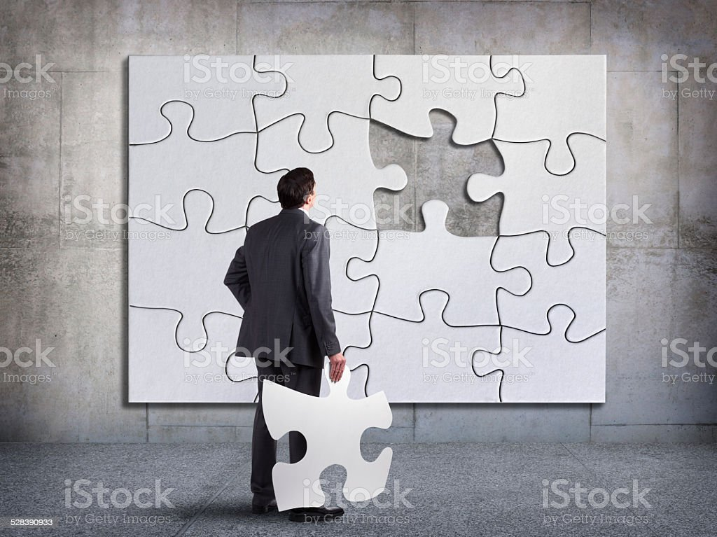 Businessman Holding Missing Piece Of The Puzzle stock photo