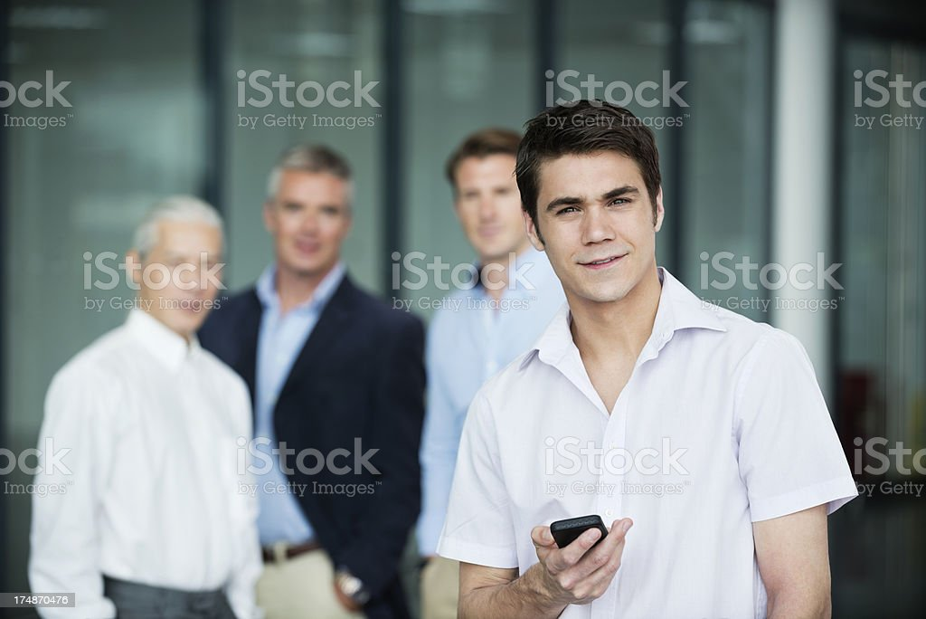 Businessman Holding Mobile Phone With Coworkers At Office royalty-free stock photo