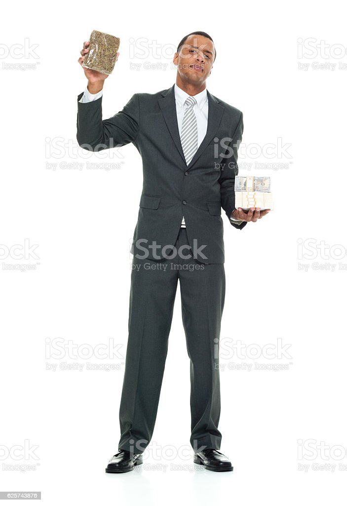 Businessman holding money and drugs stock photo