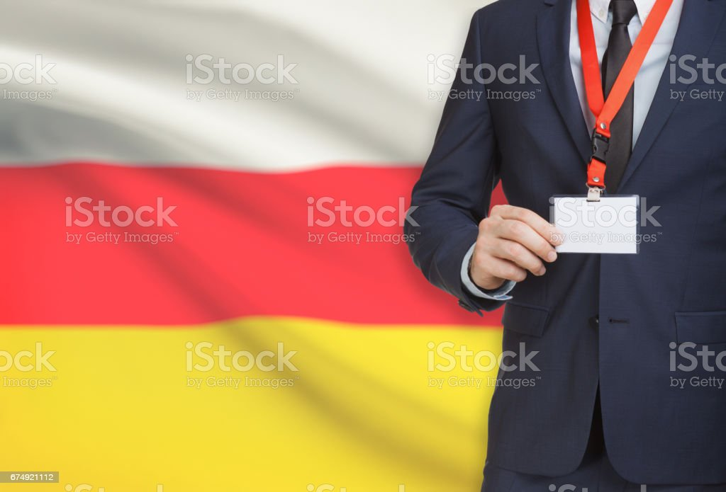 Businessman holding name card badge on a lanyard with a national flag on background - South Ossetia stock photo