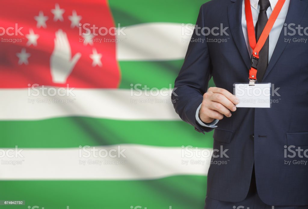 Businessman holding name card badge on a lanyard with a national flag on background - Abkhazia stock photo