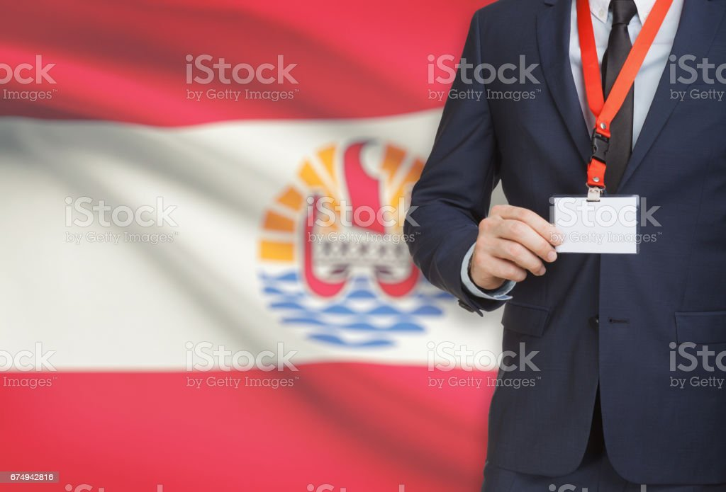 Businessman holding name card badge on a lanyard with a national flag on background - French Polynesia stock photo