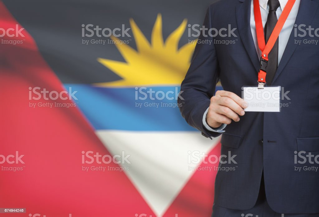 Businessman holding name card badge on a lanyard with a national flag on background - Antigua and Barbuda stock photo
