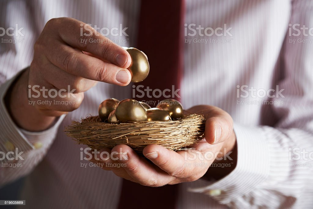 Businessman Holding Nest Full Of Golden Eggs stock photo